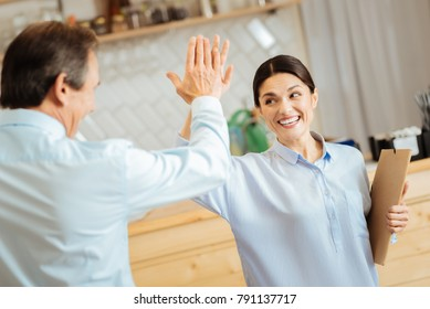 Give me five. Joyful satisfied funny colleagues holding hands up smiling and gesticulating.