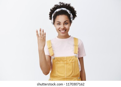 Give me four. Portrait of friendly-looking caring and cute elder sister with dark sking in trendy yellow overalls and headband over hair showing fourth number with fingers and smiling with kind smile