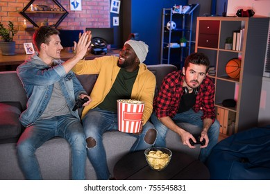 Give me high five. Positive young men are hitting their open hands in greeting each other with win while their friend is expressing disappointed while sitting on comfortable sofa and holding joystick