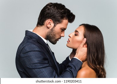 Give me a kiss. Portrait of young beautiful couple looking at their eyes while standing against white background