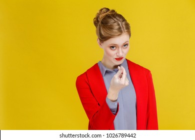Give me money, many dollars! Red hair business woman in red jacket need coin. Studio shot, isolated on yellow background