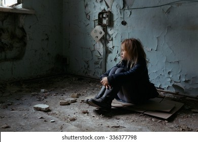 Give me support. Poor depressed little girl folding her legs and sitting on the floor while looking up