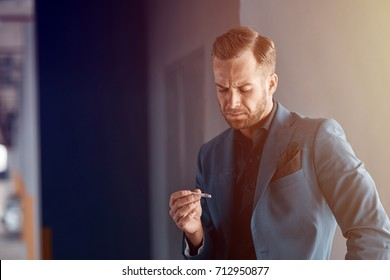 Give up smoking. Waist up of a cheerless handsome businessman holding a cigarette and feeling dissatisfied while thinking about his bad habit