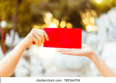 Give and take concept: Someone hold and give red envelope to their family or daughter or son and the envelope has money. It's Chinese New Year Day. It's tradition of chinese people, bokeh background