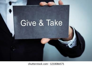 Give and Take word on cardboard.