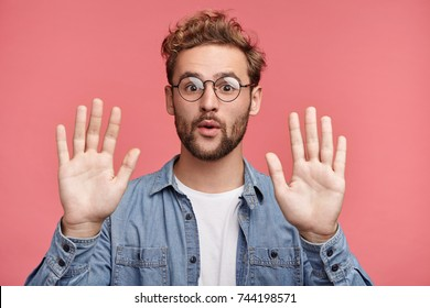 I give up! Attractive unshaven stylish man shows palms, demonstrates his innocence, surrenders, isolated over pink background. Handsome young male raises hands, looks puzzled, feels guiltless