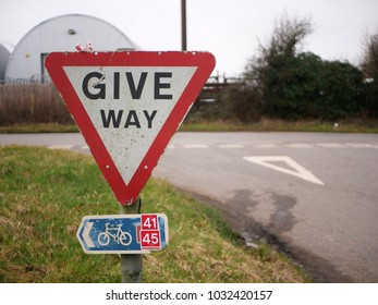 Give way sign and national cycle network sign with road markings behind in rural Gloucestershire UK