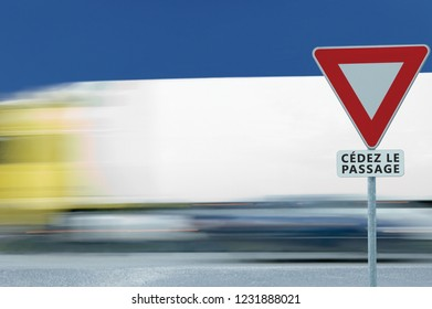 Give way text French yield road sign, cédez-le-passage, France. Motion blurred truck vehicle traffic background. Red frame triangle regulatory warning signage on pole post, bright blue summer sky.
