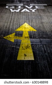 Give way yellow arrows painted on concrete road on car park floor. Dramatic dark tones vertical crop