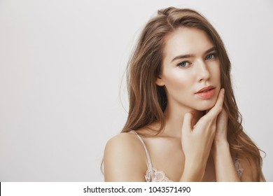 Give your skin necessary care. Studio shot of attractive european female model gently touching face, gazing sensually and flirty at camera, being in romantic and relaxed mood, standing over gray wall