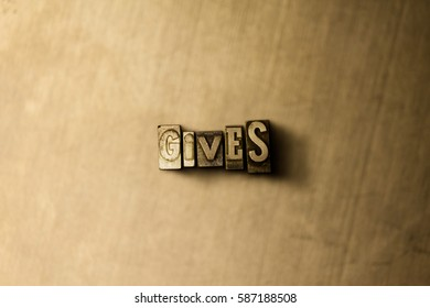 GIVES - close-up of grungy vintage typeset word on metal backdrop. Royalty free stock illustration.  Can be used for online banner ads and direct mail.