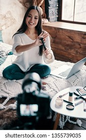Giving advice. Top view of beautiful young woman holding makeup brush and smiling while making social media video