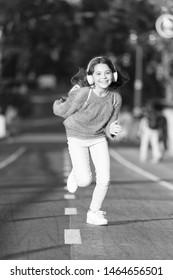 Giving all her best. Having fun. Little girl running outdoor. little girl listen music. Mp3 player. happy little girl. Audio book. Kid in headphones. Fun time. funny child. spring fun. Feeling free.