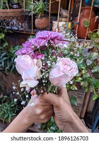 Giving a bouquet, two hands holding a bunch of flowers, Selective focus