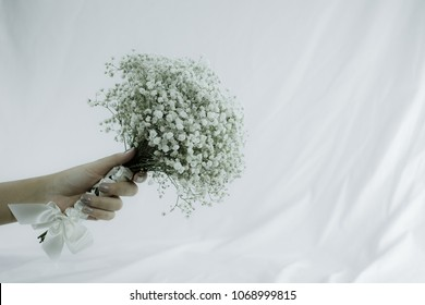 Giving bouquet of white gypsophila with white little hand