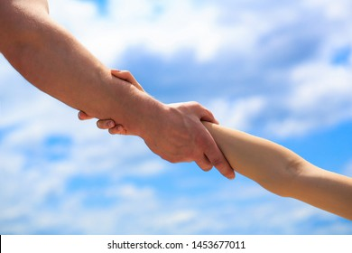 Giving a helping hand. Hands of man and woman on blue sky background. Lending a helping hand. Hands of man and woman reaching to each other, support. Solidarity, compassion, and charity, rescue.