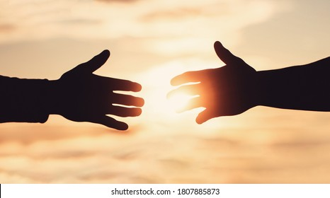 Giving a helping hand. Rescue, helping gesture or hands. Mercy, two hands silhouette on sky background, connection or help concept. The outstretched hands.