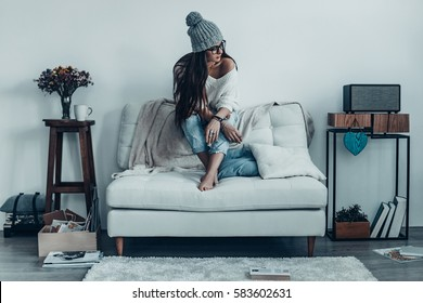 Giving herself time to dream.  Thoughtful young woman in casual wear looking away while sitting on the sofa at home