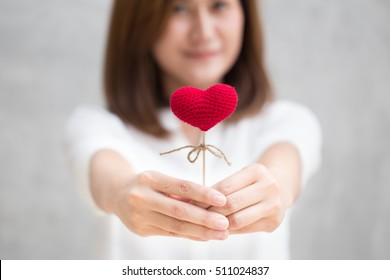 Giving love gift, Asian woman hand hold give beautiful red heart sweet loving symbol of take care or charity help to you.