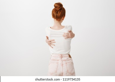 Giving myself warm hug to forget troubles. Portrait of thin young european redhead with bun hairstyle, hugging herself and standing with her back to camera, trying to comfort after mental breakdown