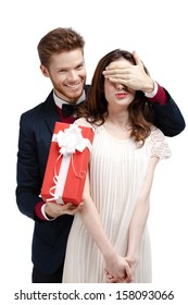 Giving a present man covers eyes of his pretty girlfriend, isolated on white