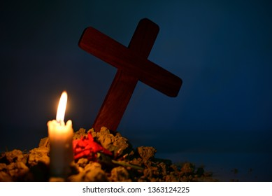 Giving respect to human soul. Give a candle and rose under Jesus cross in cemetery on moonlight.