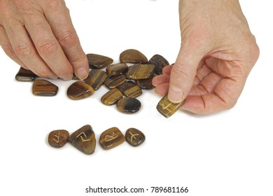 Giving a Runestone Reading - Pile of rune stones and a pair of hands picking out upturned stones isolated on a white background