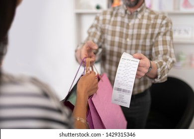 Giving shopping bags and receipt. Close-up picture of a male seller providing a client with bright shopping packages and a receipt together