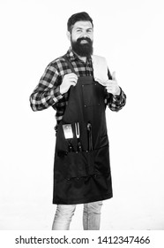 Giving thumbs up to his barbeque. Grill cook happy smiling at barbeque party. Bearded man wearing barbeque apron with grilling tools in pockets. Cooking and serving barbecue foods.