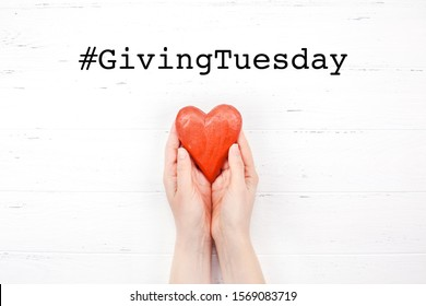 Giving Tuesday is a global day of charitable giving after Black Friday shopping day. Charity, give help, donations and support concept with text message sign and red wooden heart in woman hands