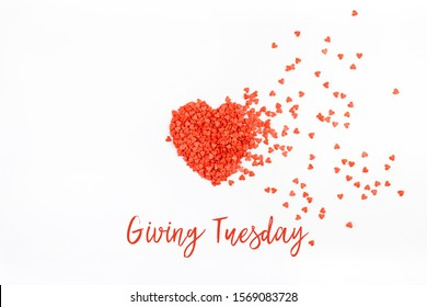 Giving Tuesday is a global day of charitable giving after Black Friday shopping day. Charity, give help, donations and support concept with text message and red heart shaped confetti white background