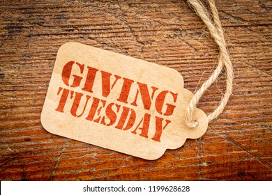Giving Tuesday sign - a paper price tag with a twine on a rustic wood