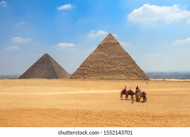 Giza, Egypt - April 19, 2019: Horse carriage with tourists in front of the Pyramid of Khufu and the Pyramid of Khafre in Egypt