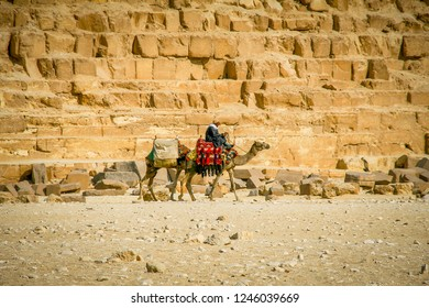 GIZA, EGYPT - DECEMBER 2, 2006: Tourist salesman on a dromedary passing the Cheops pyramid