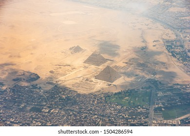 The Giza pyramid complex, also called the Giza Necropolis viewed from airplane window. Khufu, Khafre, Menkaure and Sphinx are visible.