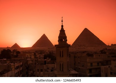 Giza pyramids with mosque in the foreground in front of orange sunset sky