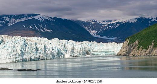 a glacial calf breaks off and splashes into the sea from the face of hubbard glacier in disenchantment bay in alaska