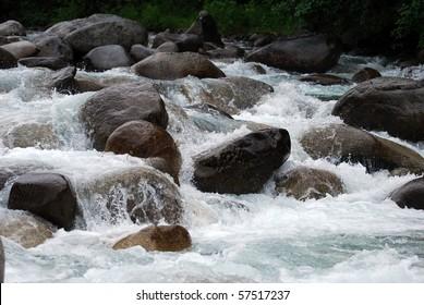 Glacial gold river rushing over boulders in Alaska