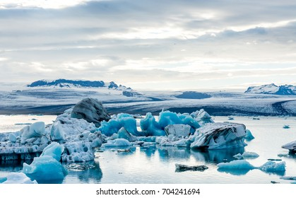 Glacial lagoon in Iceland, cloudy weather, mountains on the horizon. The glacial lake reflects the sky