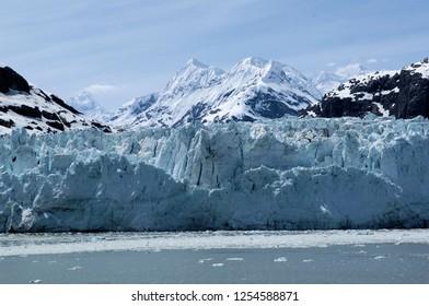 Glacier in glacier bay Alaska with mountains in background.