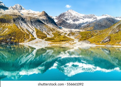 Glacier Bay National Park, Alaska, USA. Amazing glacial landscape showing mountain peaks and glaciers on clear blue sky summer day. Mirror reflection of mountains in still glacial waters.