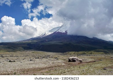 Glacier covered peak of Cotopaxi Volcano, partially hidden by clouds, above a desolate, high altitude plain covered in large rocks and scrub grass