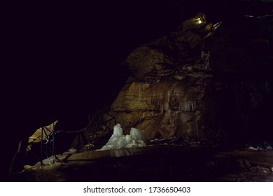 Glacier in a deep dark cave in the old mountain. Clear water froze among the dark walls of the rock in the dungeon. Natural refrigerator in nature. Landscape orientation
