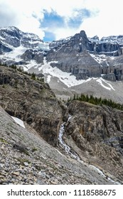 Glacier hanging high in the mountains and waterfall in the middle of the big cliff. Green pines around the waterfall. Mighty Stanley glacier with blue sky and clouds in Kootenay national park.