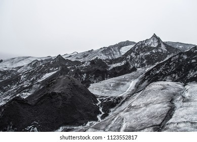 Sólheimajökull Glacier in Iceland showing ash piles on the ice.