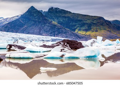 The glacier in Iceland - Vatnajokull  in the summer. Huge ice floes have broken away from a glacier and drift towards the ocean. The concept of northern extreme tourism