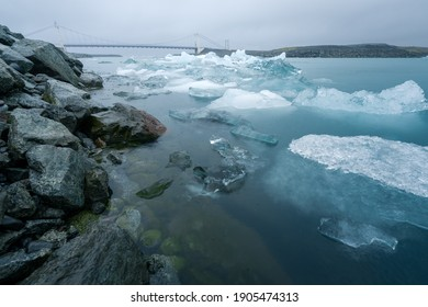 Glacier lagoon with floating icebergs and suspension bridge in the background. Jokulsarlon, southern Iceland.