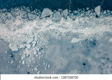 Glacier Lagoon with icebergs from above. Aerial View. Cracked Ice from drone view. Background texture concept.