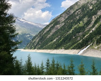 Glacier lake in austria with a tree on the foreground and mountains in the background. Cloudy blue sky, picture taken in zillertal