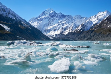 Glacier lake with ice blocks and background of misty Mount Cook shot during early spring